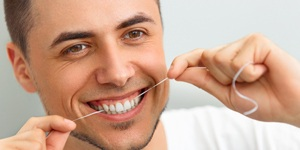 A guy flossing his teeth